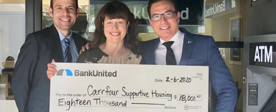 "Carrfour President/CEO Stephanie Berman-Eisenberg, center, accepts $18,000 BankUnited ""Go for More"" contribution."